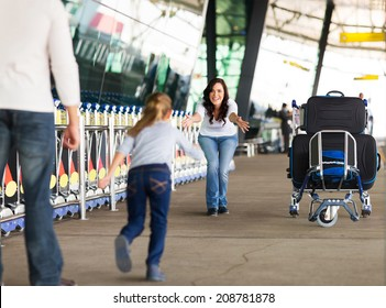 young girl running to her mother at airport after a long wait with her father