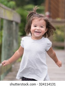 Young girl running on dock, with a big smile.