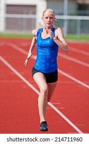 A young girl running on a track towards the camera.