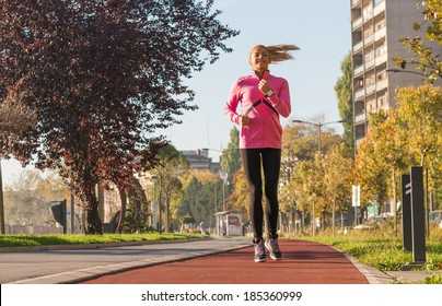 A young girl running outdoors in city
