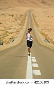 Young girl running over a desert highway.