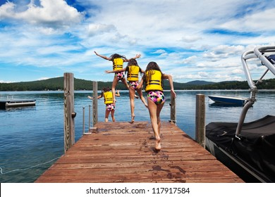 Young girl runs down the dock to jump to a warm summer lake