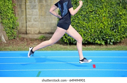 Young girl runs fast on the athletics track during sports training