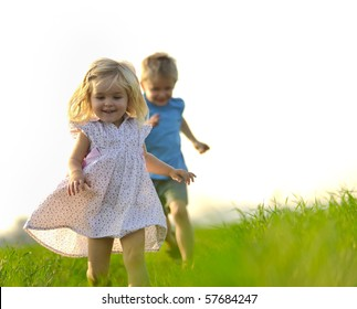 Young girl runs through a field, happy and having fun.