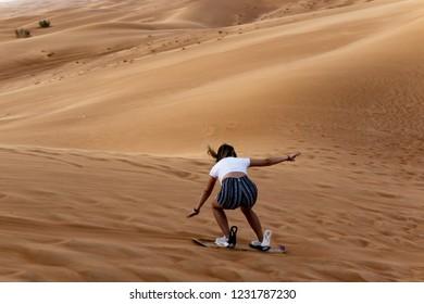 Young girl sandboarding in the desert - extreme desert activity