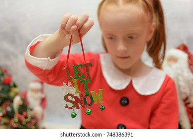 Young girl in Santa Claus suit playing with a Christmas decoration. Decoration reads 'let it snow' decoration is in focus with little girl blurred in the background