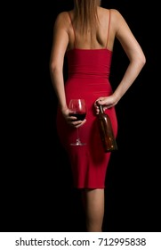 A young girl in a scarlet dress hides behind her a full glass of wine and an empty bottle