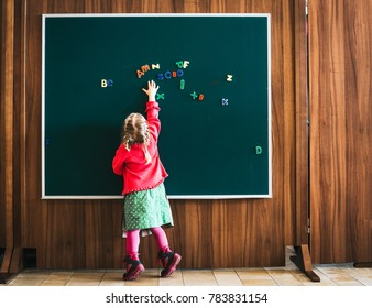 young girl in a school with some letters on blackboard