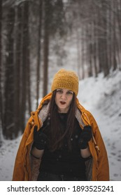 young girl scolds her partner while taking pictures in the winter. A woman aged 20-24 in a yellow jacket and black gloves stands on a snowy road. Portrait in antique white tones.
