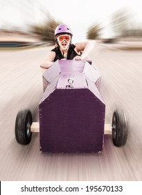 young girl screaming as she's rolling down a hill in a homemade soap-box car