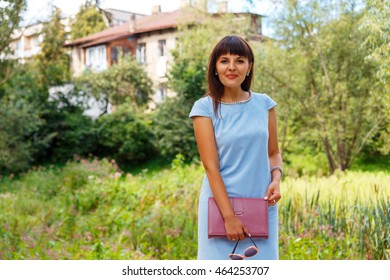 A young girl selling agent real estate posing on the background of the house