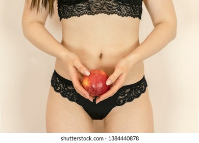 A young girl in sexy black underwear is holding a red apple. The Forbidden fruit.