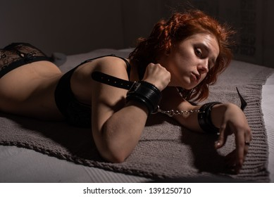 A young girl in sexy lingerie, lying on the bed handcuffed. BDSM games and entertainment. Sexual perversion.