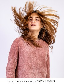 Young Girl shaking her head with hair ruffled by the wind