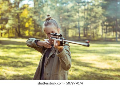 Young girl shooting from the air rifle in the forest