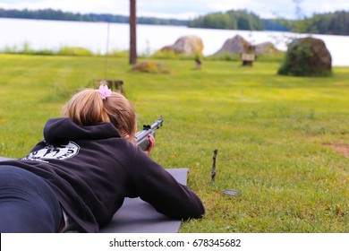 A young girl shooting an air rifle at a target.