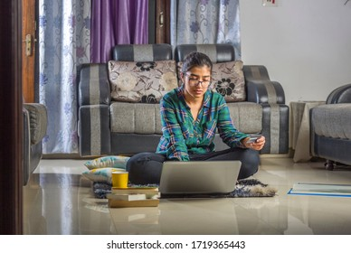 a young girl is shopping online using credit card with laptop sitting on floor