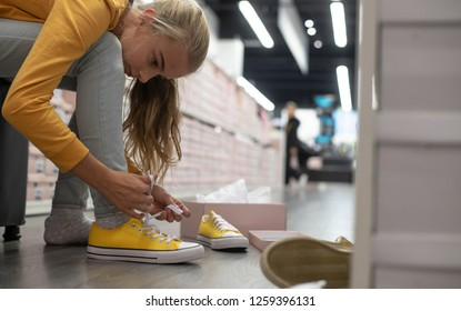 Young girl shopping in shoe store trying on shoes