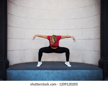 Young girl with short hair, dressed in red blouse and black leggings, is dancing in front of the stone wall