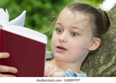 A young girl showing emotion whilst reading a book.