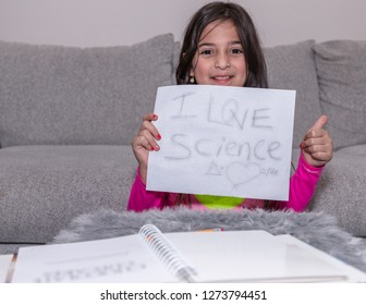 "A young girl is showing a sign saying stating ""I Love Science"""
