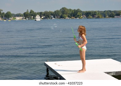 a young girl shows off her bubble making ability at the lake