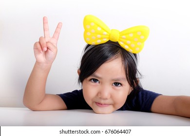 Young girl shows peace hand sign