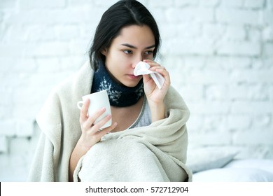 Young girl sick in bed with temperature drinks hot
