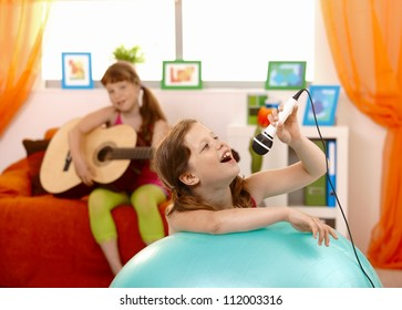 Young girl singing into microphone, having fun with guitar player friend at home.