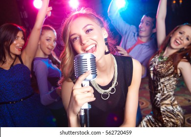 Young girl singing into  microphone at  party