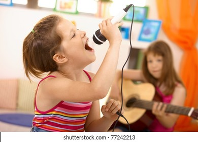 Young girl singing with microphone at home, concentrating, other girl playing guitar in background.?