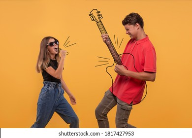 A young girl sings into an imaginary microphone, a guy emotionally plays an imaginary guitar  against yellow background in studio