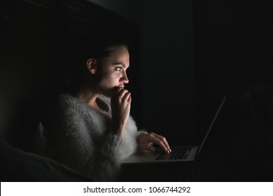 young girl sits in the dark at night, enthusiastically watches TV series on laptop