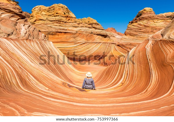 A young girl sits with her back to the camera in the central part in Wave Canyon, North Coyote Buttes, Arizona, USA