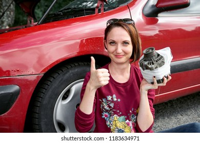 a young girl sits near a broken car and makes repairs to the electric generator, fixed it with a bandage and shows a successful gesture