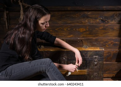 Young girl sits near a chest and trying to solve a conundrum to get out of the trap, escape the room game concept