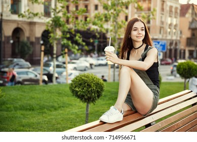A young girl sits on a bench in the city, with a drink in her hand.