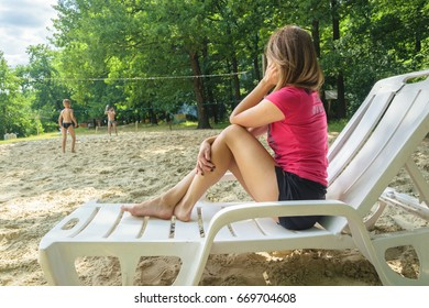 A young girl sits on a deckchair on the beach and watches the children playing volleyball. Kreminna, Ukraine 26.06.2017
