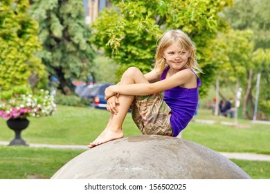 A young girl sits on a man made rock to take a break at an outdoor park just watching the world pass by while a light summer breeze rustles her hair.