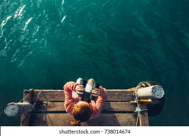 Young Girl Sits On The Pier And Looks At Sea Through Binoculars, Top View. Adventure Vacation Discovery Travel Concept