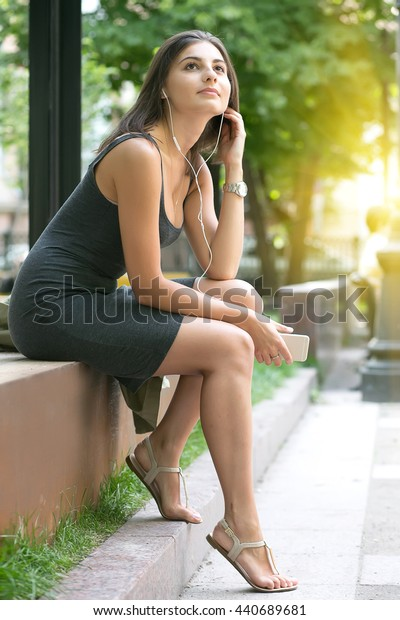 The young girl sits in park with earphones and listens to music