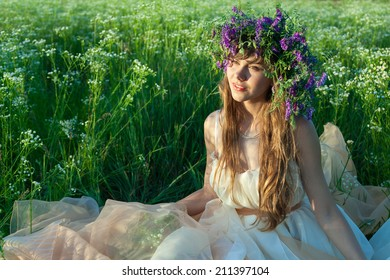 Young girl sitting in amongst the flowers and grass in the field.