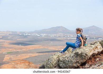 Young girl sitting with backpack on cliff's edge and looking to a sky. Lanzarote