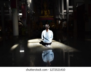 young girl sitting in bright sun light in front of main Buddha image in Buddhist temple