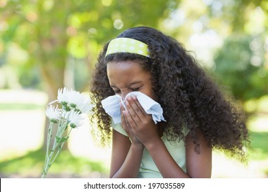 Young girl sitting by flower and blowing her nose in the park on a sunny day