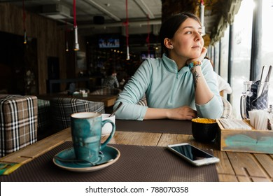 A young girl is sitting in a cafe, warming herself and looking thoughtfully out the window