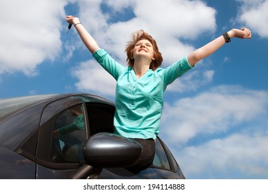 young girl sitting in the car and holding a key against blue sky