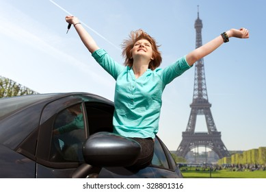 young girl sitting in the car and holding a key against blue sky in Paris, France, next to Eiffel tower