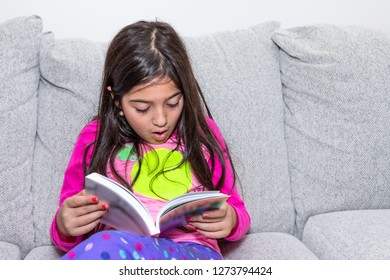 A young girl sitting in a couch is reading a book