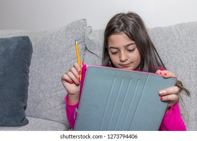 A young girl sitting in a couch, is thinking while playing with her tablet